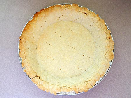 A cooked pie crust in a pie pan