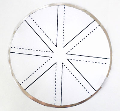 A paper windmill template is taped to an aluminum circle