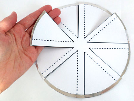Cuts are made to an aluminum circle following a paper windmill template that is taped on