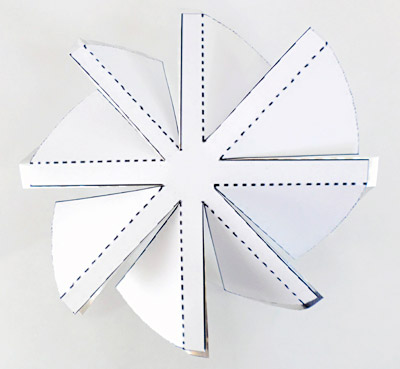 Angled fan blades are made by folding sections of cut aluminum along the lines of a template
