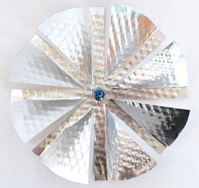 Top-down view of a straw inside a nut placed on the center of an aluminum windmill