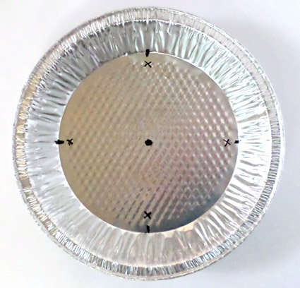 An aluminum pie pan has five black dots marked at the north, east, south, west and center of the pan