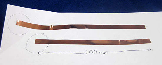 Two strips of copper tape of different lengths on a piece of paper