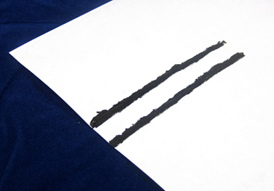 Two parallel lines of black paint on a piece of paper