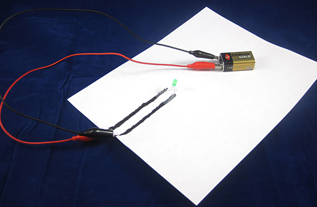 A paper circuit made from a battery, alligator clips, electric paint and an LED