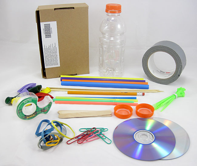 Cardboard, tape, a bottle, straws, balloons, zip ties, bottle caps, CD's, rubber bands, and paper clips
