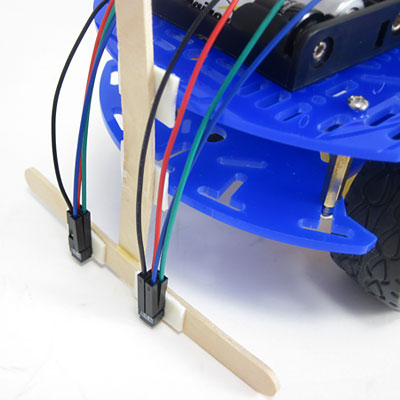Popsicle sticks and double side tape are used to mount IR sensors to the front of a line-following robot
