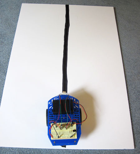 A line-following robot is placed on a white paper with a large black line drawn straight across
