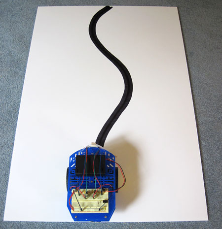 A line-following robot is placed on a white paper with a large black line drawn with multiple curves