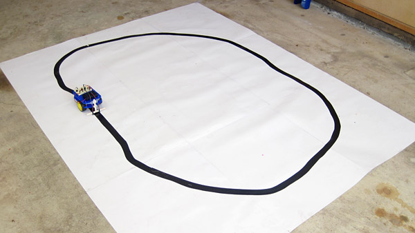 A line-following robot is placed on a sheet of white paper with a large circle drawn in black ink