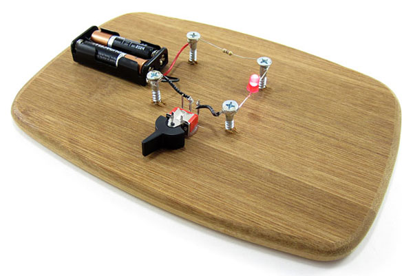 A switch, battery pack, resistor and LED are attached to a wooden board with screws