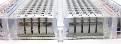 Rows of spring clips are visible inside a transparent breadboard