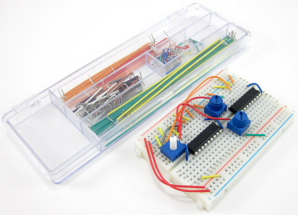 A wired breadboard next to a container filled with flexible jumper wires of different sizes
