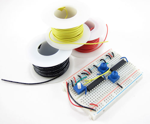 A wired breadboard next to three spools of yellow, red and black hookup wire
