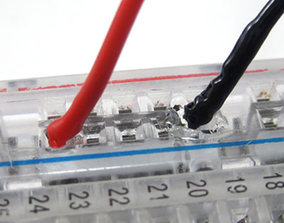Close-up photo of melted plastic and insulation where a wire connects to a breadboard