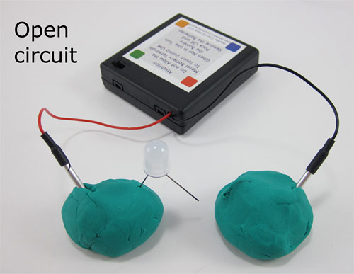 Two leads of a battery pack are inserted into two separate balls of Play-Doh, one of which has an LED partially inserted
