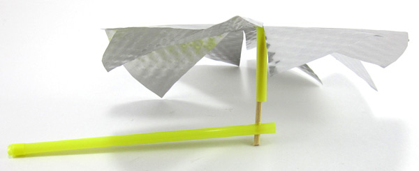 A pinwheel is made from a cut aluminum plate, straws and a toothpick