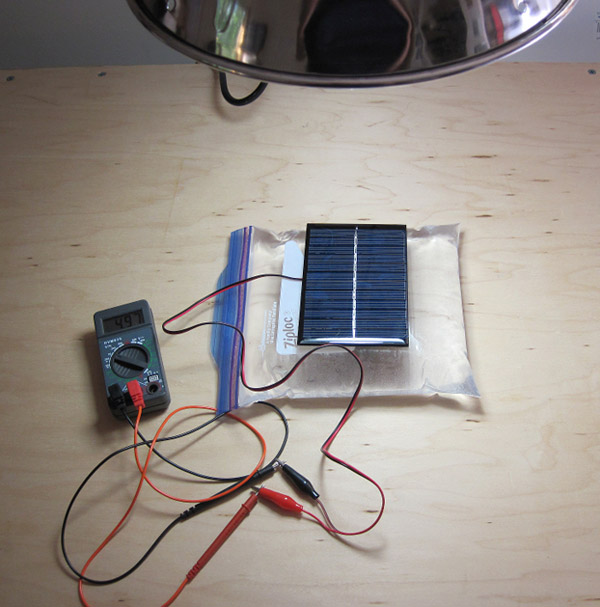 A multimeter connects to a solar cell resting on a bag of water