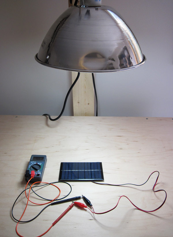 A lamp shines on a solar panel that is connected to a multimeter