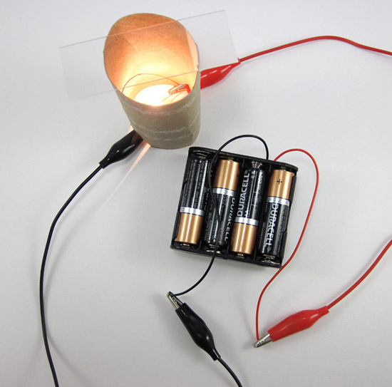An enclosed lightbulb is connected to a battery pack with two wires