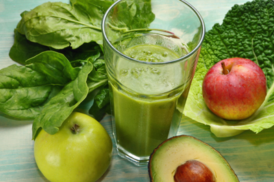 Green smoothie surrounded by fruits and vegetables