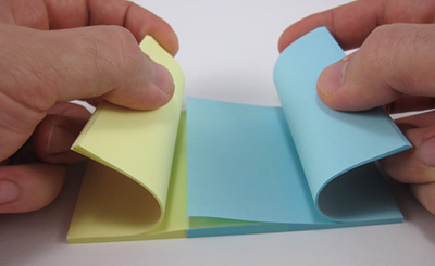 A blue and yellow paper pad have their pages interlaced one by one