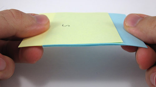 Two pads of blue and yellow paper with the paper from both interlaced