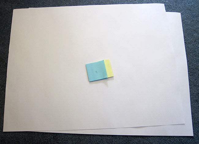 Two pads of blue and yellow paper with the paper interlaced on a piece of poster board