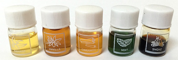 Five vials of concentrated scent solutions of banana, vanilla, cinnamon, mint and smoke