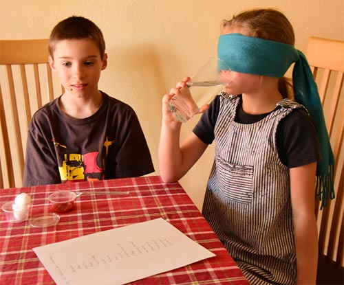 A child sits at a table with another child who is blindfolded and is taking a sip of water