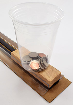 A cup of coins rests on a model maglev train