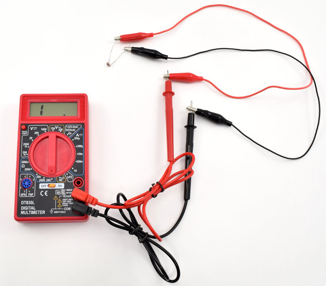 Alligator clips connect the leads of a photoresistor to the probes of a multimeter