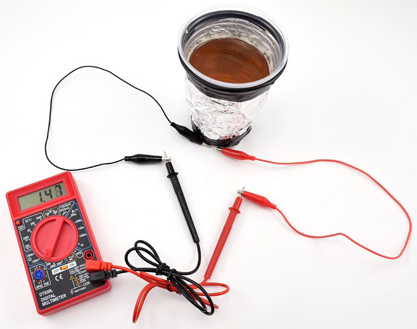 Multimeter probes connect to two leads of a photoresistor that is embedded in the bottom of a cup wrapped in foil