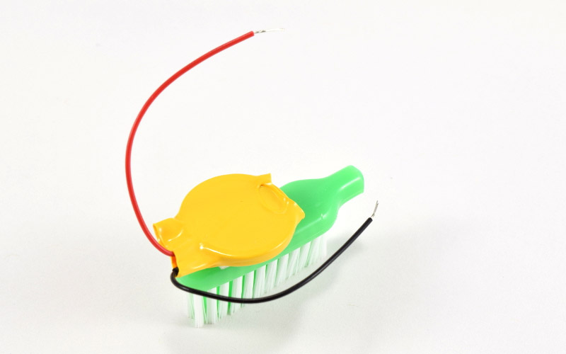 Battery attached to toothbrush.
