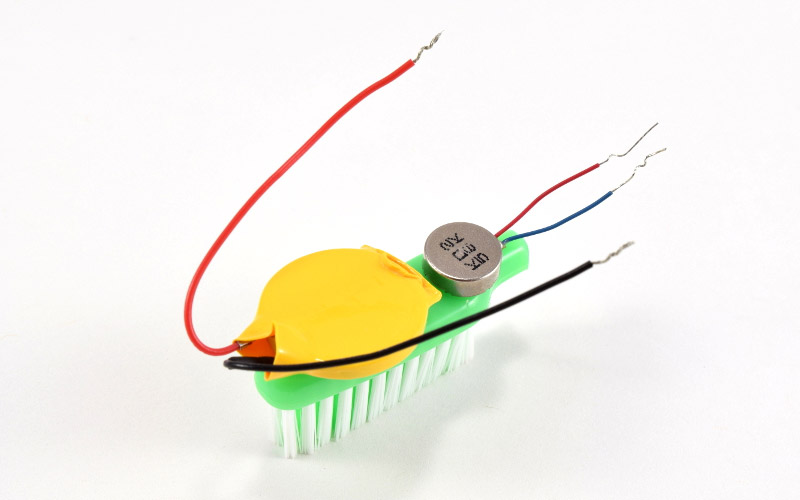 Battery and motor attached to toothbrush.
