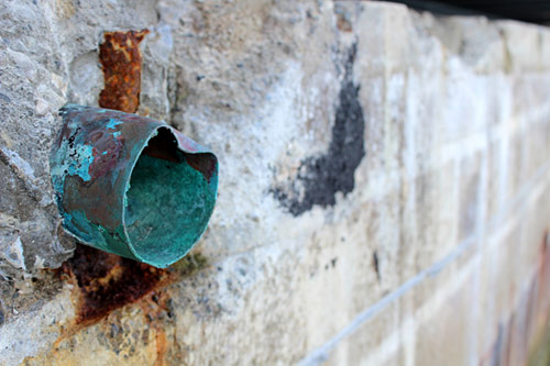Copper pipe in a wall showing signs of corrosion.