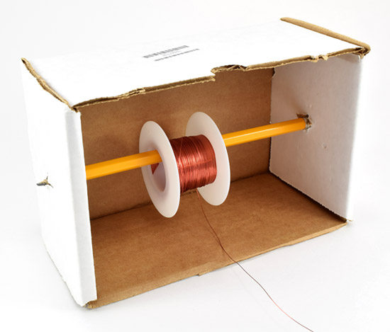 A wire spool hangs from a pencil that is pierced through the walls of a cardboard box