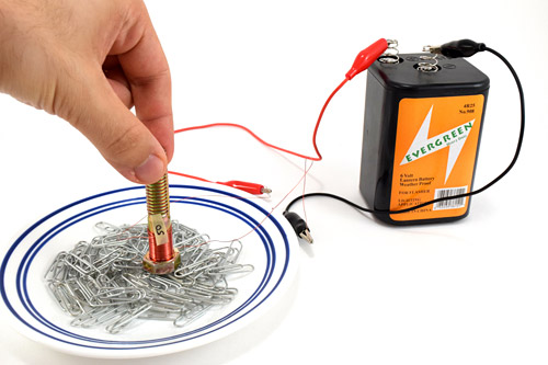 A small electromagnet presses against paperclips in a bowl