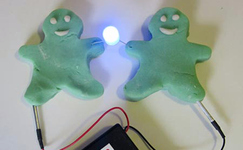 Squishy circuit cookie cutouts holding hands with LED