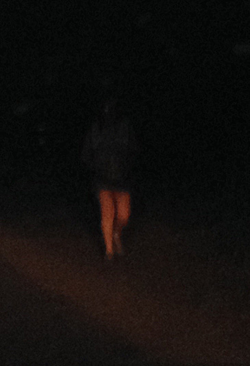 Photo of a jogger barely visible in the dark