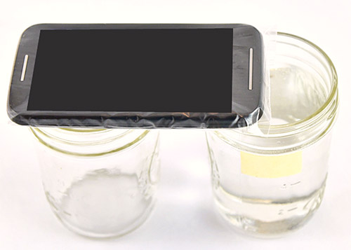 A smartphone in a plastic bag is placed on the rim of a glass jar so the microphone is above the rim of a second glass jar