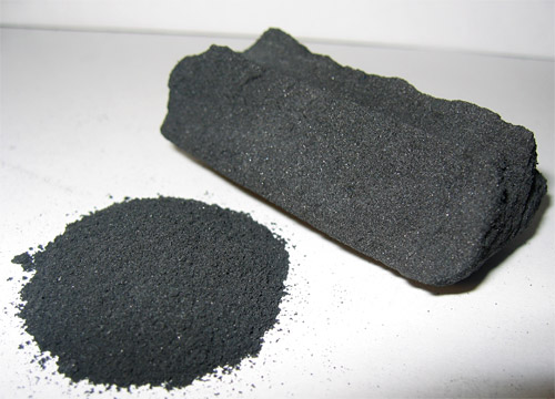 A pile of activated carbon powder next to a block of activated carbon