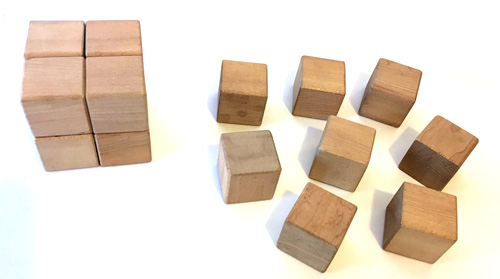Eight small cubes form a larger cube next to eight small cubes spread out on a table