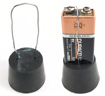 A wire loop inserted into a rubber stopper holds a 9 volt battery in place