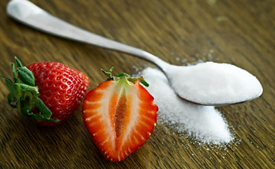A strawberry next to a spoon full of sugar.