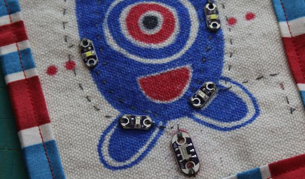 Five LilyPad LEDs sewn into a cloth fabric