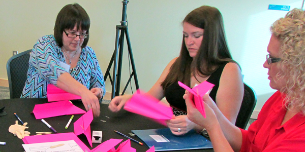 Three woman fold pink paper airplanes