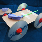 A balloon powered car made from cardboard, tape, CDs, wooden skewers, a straw and a balloon